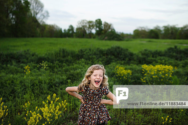 Portrait of girl with wavy blond hair laughing in field