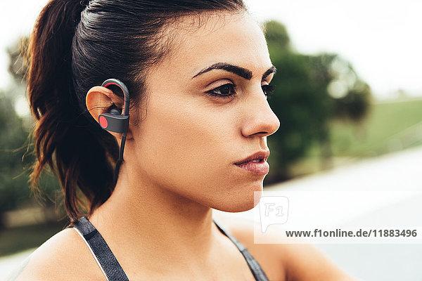 Porträt einer jungen Frau im Freien  mit Kopfhörern in Nahaufnahme  South Point Park  Miami Beach  Florida  USA