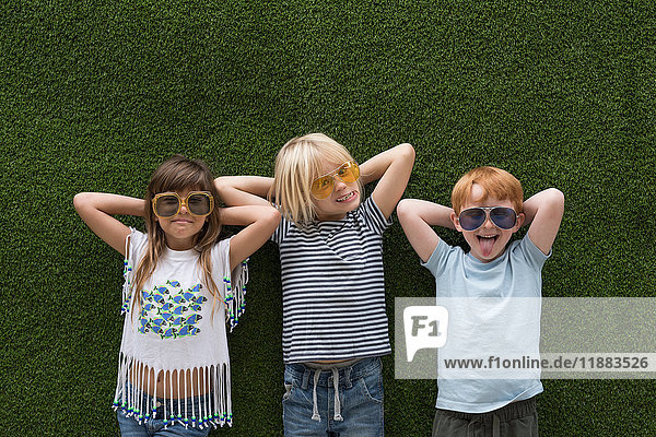 Children in front of artificial turf wall  hand behind head wearing sunglasses
