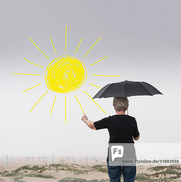 Senior woman with umbrella drawing sun in air
