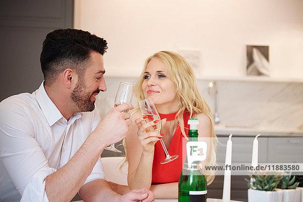 Ein Paar  das sich eine Flasche Champagner teilt und einen Toast ausbringt