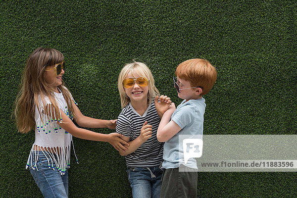 Children in front of artificial turf wall playing tickle