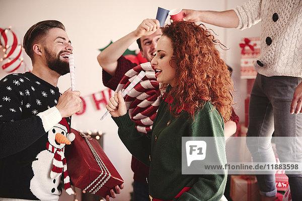 Junge Männer und Frauen singen auf der Weihnachtsfeier mit Scheinmikrofonen