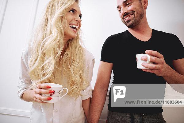 Paar zu Hause mit Kaffee  Hände haltend  Gesicht an Gesicht lächelnd
