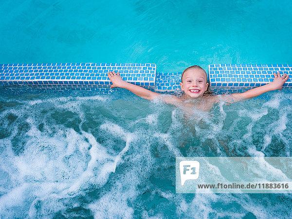 Overhead portrait of cute boy splashing in outdoor swimming pool