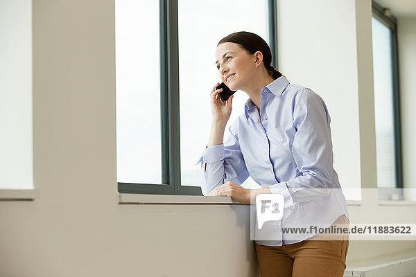 Frau  die in einem leeren Büro am Fenster steht und ein Smartphone benutzt