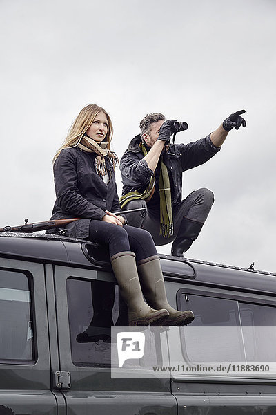 Hunting couple  on top of off road vehicle with shot gun and binoculars