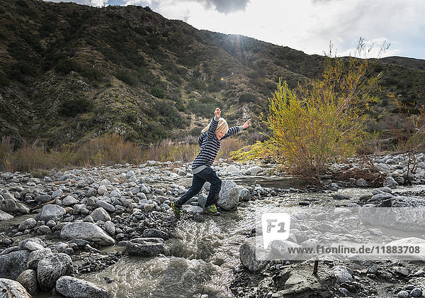 Boy leaping over rocks on riverbed