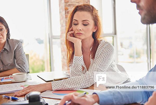 Geschäftsfrau in Besprechung Hand am Kinn nachdenklich schauend