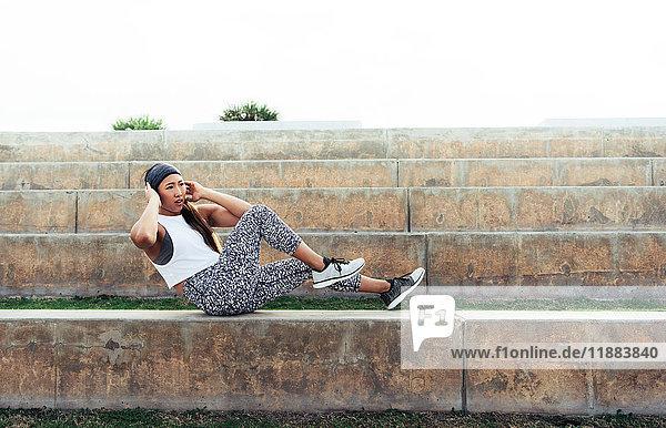 Junge Frau übt im Freien  macht Sit-ups auf der Stufe  South Point Park  Miami Beach  Florida  USA