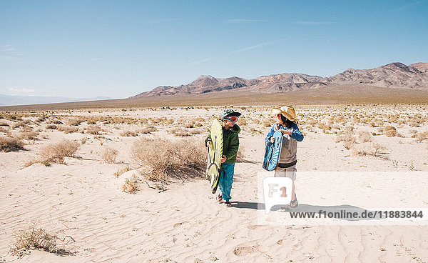 Two boys walking together Eureka Dunes  Death Valley National Park  California  USA