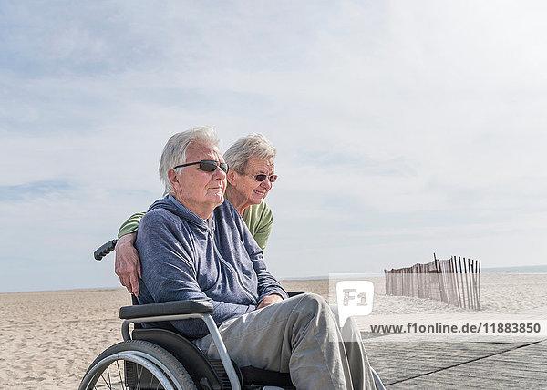 Senior man in wheelchair with wife at beach  Santa Monica  California  USA