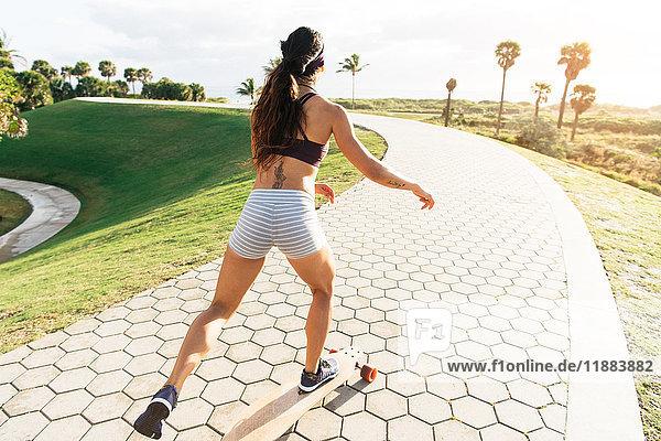 Junge Frau beim Skateboarden im Park  Rückansicht  South Point Park  Miami Beach  Florida  USA