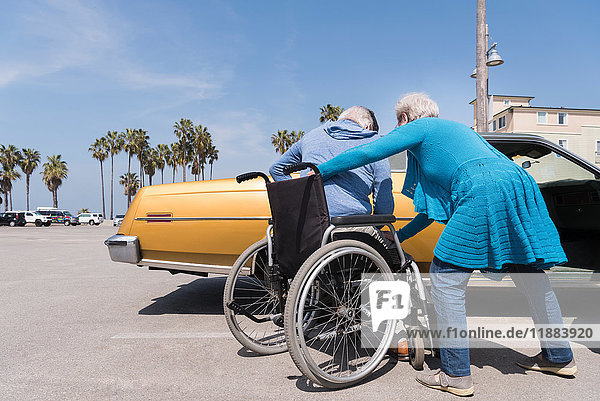 Senior woman helping husband in wheelchair by vintage car at Venice Beach  California  USA