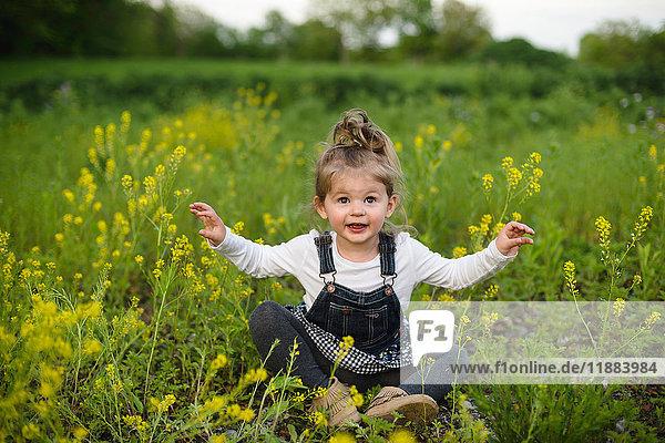 Portrait of girl cross legged in wildflower meadow
