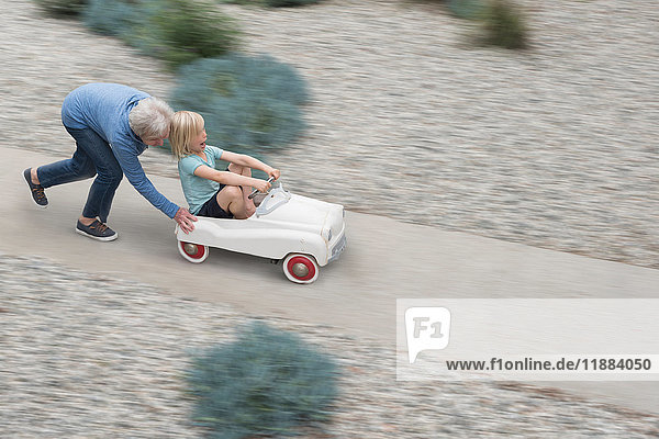 Grandmother pushing grandson on his toy car
