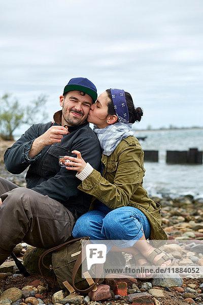 Junge Frau küsst am Strand ihren Freund auf die Wange