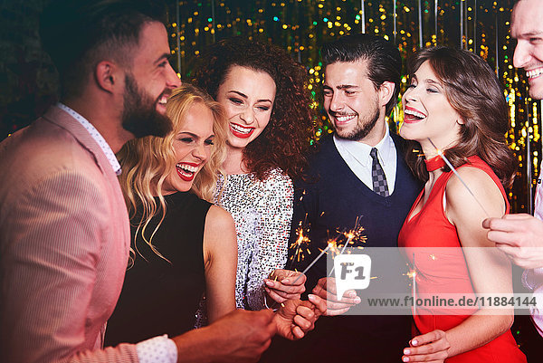 Group of people at party  holding sparklers  laughing