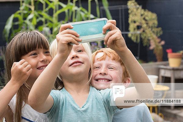Smiling children taking selfie