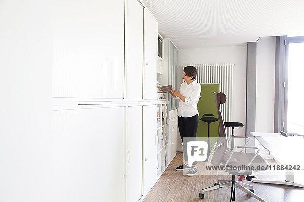 Junge weibliche Verkaufsleiterin betrachtet Verkaufsbroschüre im Büromöbelgeschäft