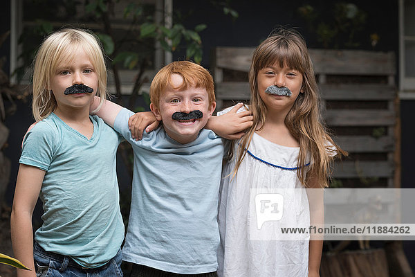 Children wearing fake mustaches looking at camera smiling