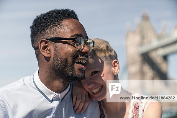 Young couple laughing together outdoors  Tower Bridge in background  London  England  UK