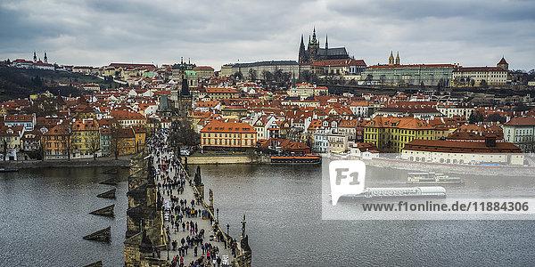 'Pedestrians on Charles Bridge over the Vltava River and Prague Castle in the distance; Prague  Czech Republic'