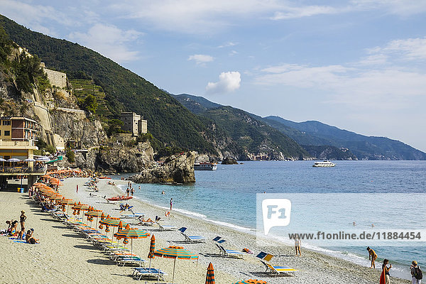 'Beach with orange umbrellas at Monterosso village  part of the Cinque Terre hamlets on the Italian Riviera coastline; Monterosso  La Spezia  Italy'