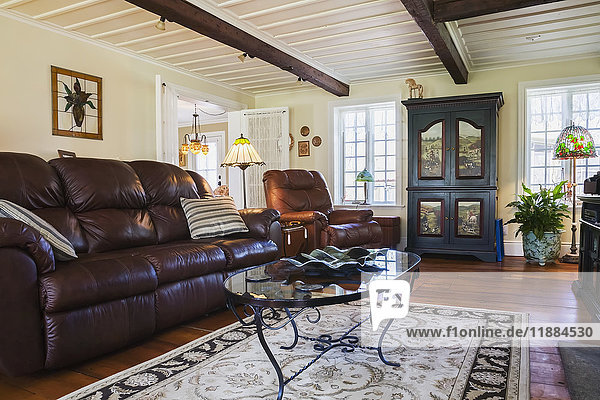 'Brown leather sofa  chair and wooden armoire in the living room inside an old reconstructed 1886 Canadiana cottage style residential home; Quebec  Canada'
