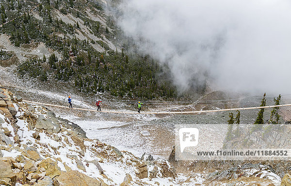 'A group of rock climbers walk across the suspension bridge at Kicking Horse Mountain to reach their climbing trail; Golden  British Columbia  Canada'