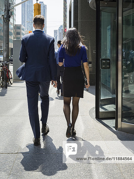 'Rear view of a businessman and businesswoman walking down the sidewalk in downtown Toronto; Toronto  Ontario  Canada'