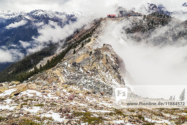 'At the summit of the hiking trail on Kicking Horse Mountain  the gondola and ski lodge destination for the return hike are seen in the far distance in the clouds  Kicking Horse Mountain resort in the summer; Golden  British Columbia  Canada'