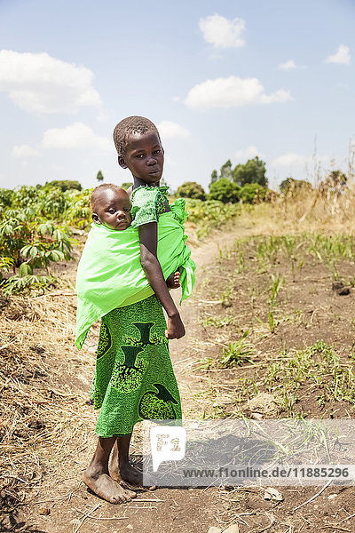 'A young girl carries a baby on her back in a sling; Uganda' 'A young girl carries a baby on her back in a sling; Uganda'
