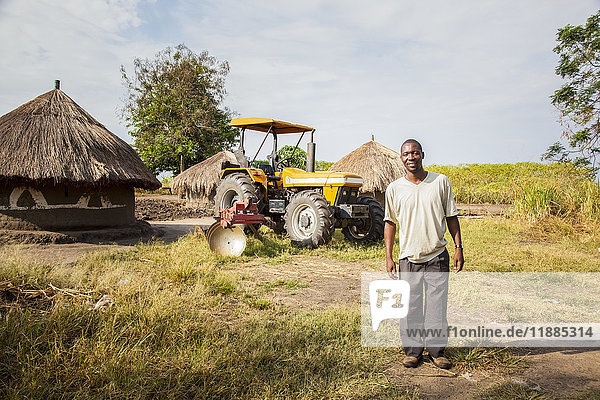 'A man stands posing with a tractor and hut in the background; Uganda'