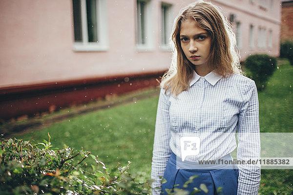 Porträt eines jungen Mädchens  das bei Pflanzen gegen das Bauen im Regen steht.