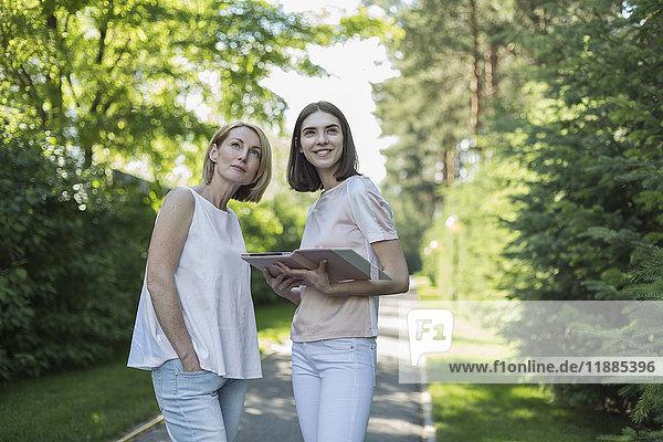 Tochter hält digitales Tablett  während sie mit ihrer Mutter inmitten von Bäumen im Park aufblickt. Tochter hält digitales Tablett, während sie mit ihrer Mutter inmitten von Bäumen im Park aufblickt.