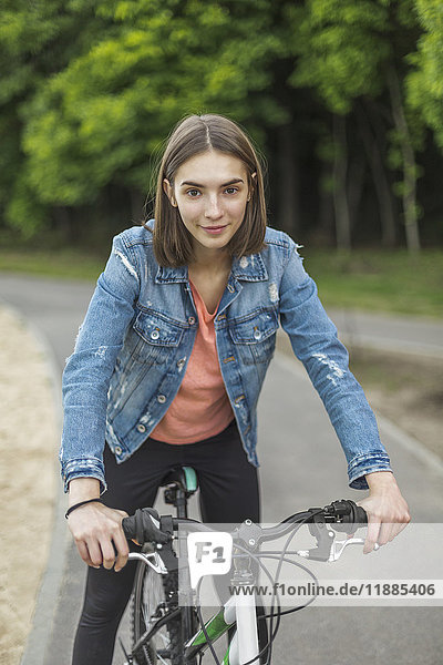 Porträt einer lächelnden Frau beim Radfahren auf der Straße im Park