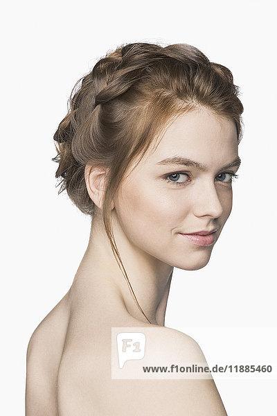 Porträt einer schönen Frau ohne Hemd  die vor weißem Hintergrund lächelt.