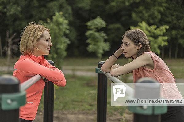 Seitenansicht von Mutter und Tochter am Geländer im Park