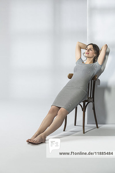 Junge Frau auf Stuhl liegend vor weißem Hintergrund