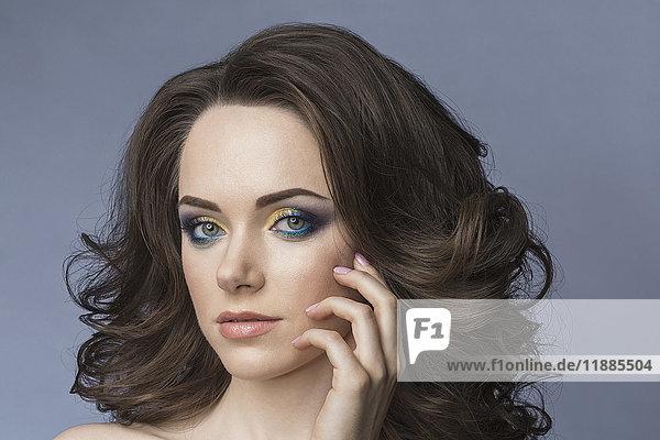 Nahporträt einer jungen Frau mit Augen-Make-up vor grauem Hintergrund