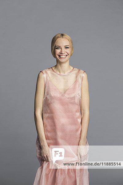 Porträt einer jungen Frau im rosa Kleid vor grauem Hintergrund
