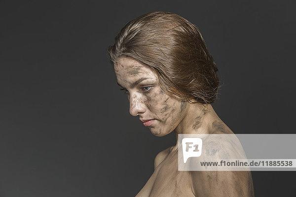 Nahaufnahme einer schmutzigen  nackten Frau  die auf einen grauen Hintergrund blickt.