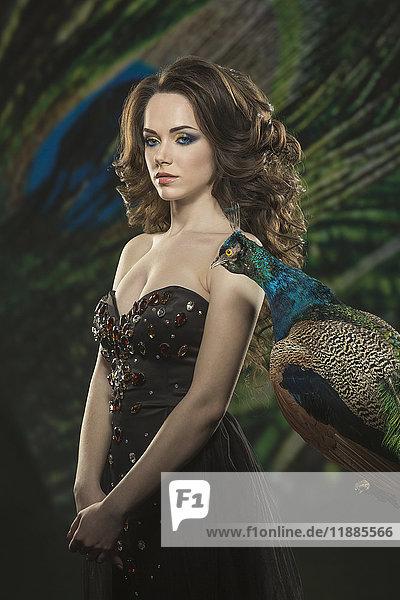Frau trägt trägerloses Kleid  während sie am Pfau gegen Federn steht.