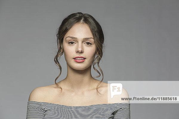 Porträt einer selbstbewusst schönen Frau vor grauem Hintergrund