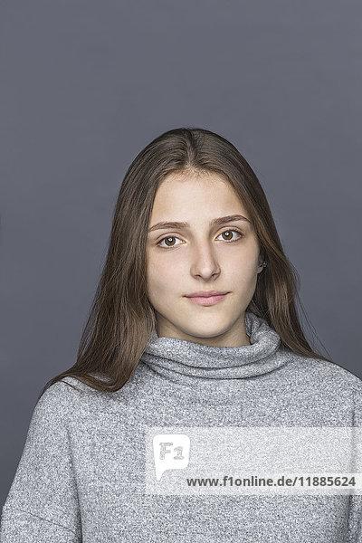 Porträt eines Teenagermädchens vor grauem Hintergrund