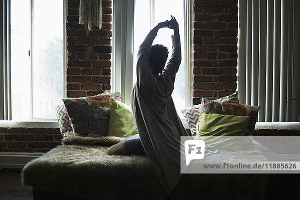 Rückansicht der Frau  die sich zu Hause auf dem Bett ausstreckt