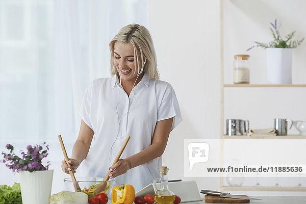 Glückliche schöne Frau  die Musik hört und Salat in der Schüssel an der Küchentheke gegen die Wand wirft.