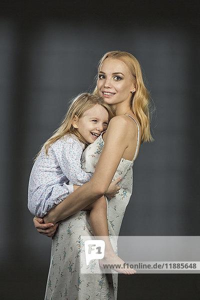 Seitenansicht Porträt der Mutter mit Tochter vor schwarzem Hintergrund