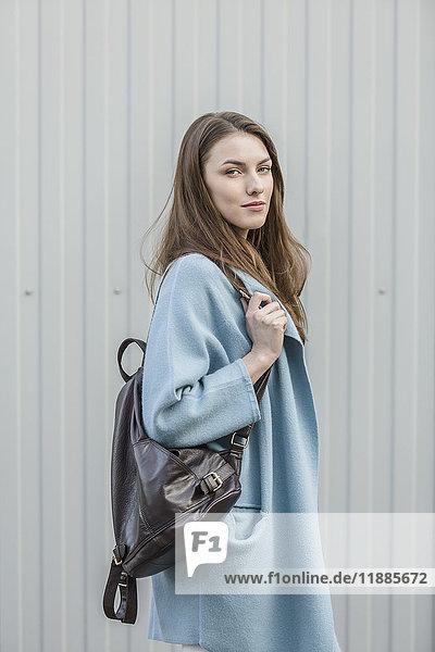 Porträt der schönen Frau mit Rucksack an der Wand stehend Porträt der schönen Frau mit Rucksack an der Wand stehend